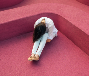 Woman sitting on a pink floor hugging her knees