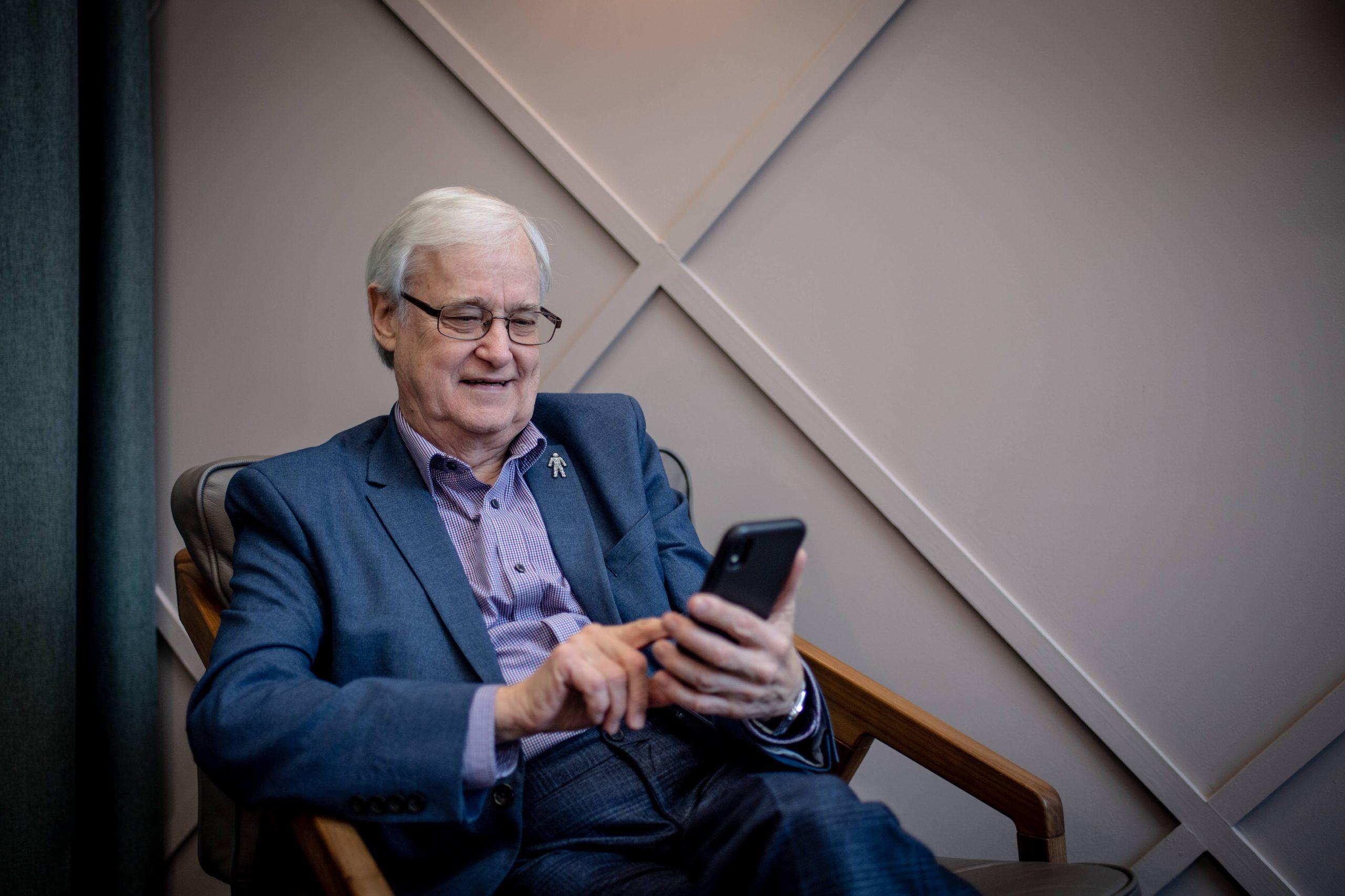 Older man with prostate cancer badge on a smartphone