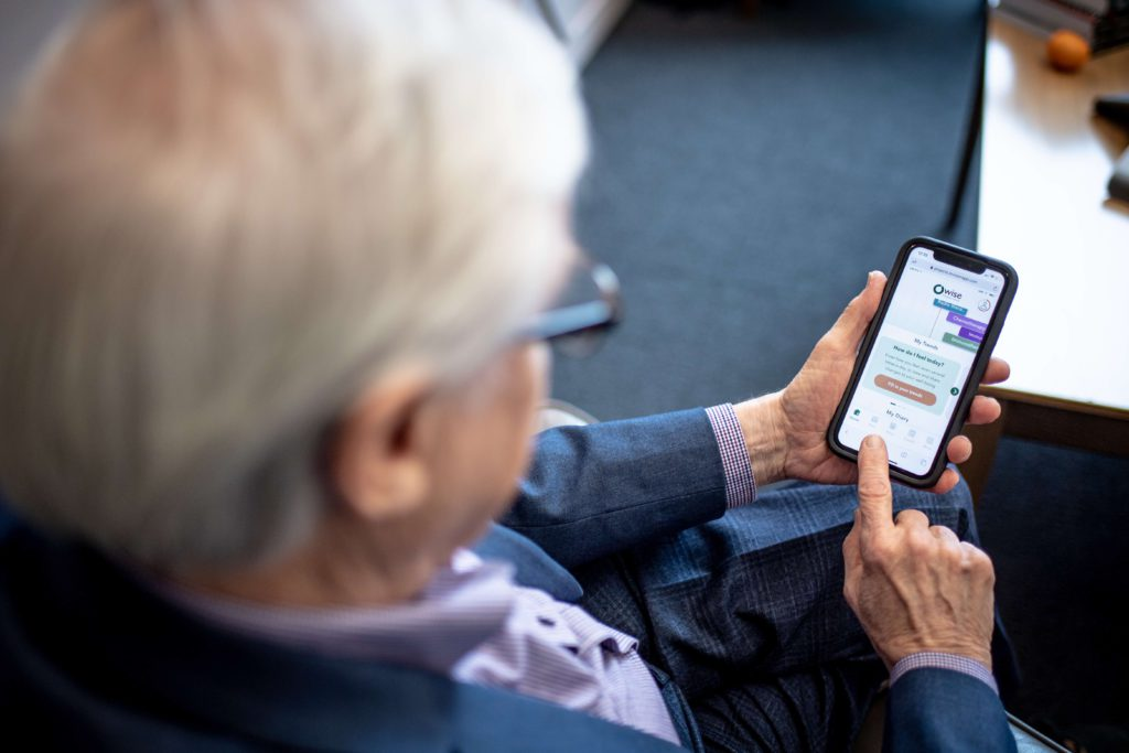 Older man trials OWise prostate cancer app on his smartphone.